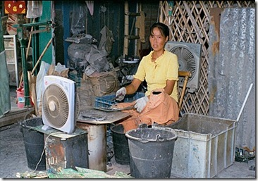 Chinese woman smelts computer circuit boards over an open stove to extract metals. The fan is an attempt to disperse the highly toxic fumes created by the smelting.